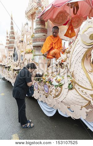Suratthani, Thailand - October 20, 2016: Buddhist monk sitting on ornamented carriers to be pulled across the city during the famous Chak Phra Festival, an annual Buddhist festival to celebrate the return of Buddha from heaven to earth after the end of th