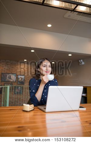 Beautiful cute asian young businesswoman in the cafe using laptop and drinking coffee smiling