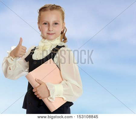 Dressy girl schoolgirl in black dress and white blouse holding a textbook and shows thumb. Gesture all right. Close-up.