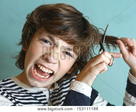 naughty kid cutting hair to himself with scissors funny look