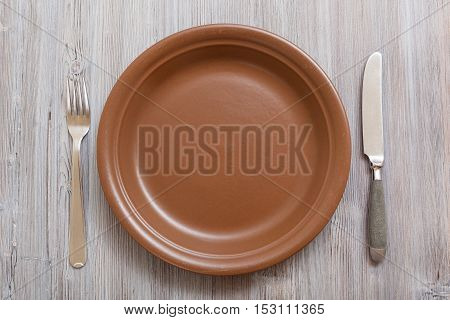 Top View Of Brown Plate, Knife Spoon On Gray Brown