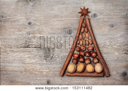 Christmas spices and nuts in the form a Christmas tree on the old wooden background