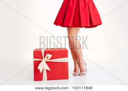 Cropped image of a woman in red mini dress standing with big gift box isolated on a white background