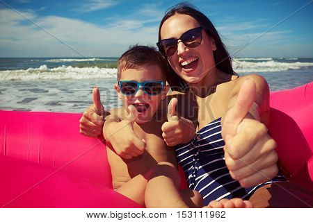 Mid shot of the happy family who are sitting on the rubber raft on the beach and holding their thumbs-up on a gorgeous sunny day. Enjoying time together