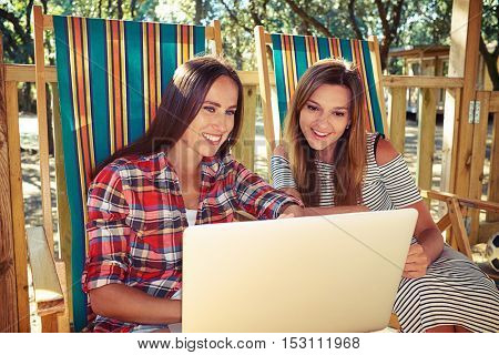 Mid shot of two best friends sitting and smiling when point at the screen of computer. Spending time together, having rest during vacation. Sitting on a comfortable striped summer beach chair