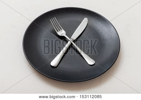 Black Plate With Crossing Knife, Spoon On White