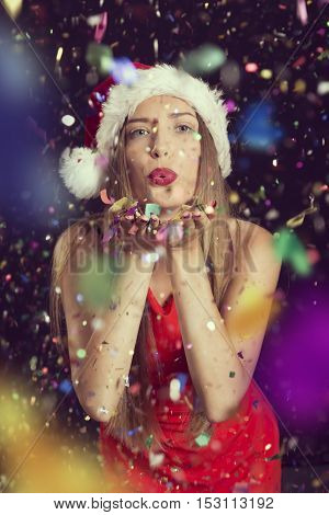Beautiful young woman wearing Santa's hat having fun at a New Year's Eve party blowing away confetti and sending kisses