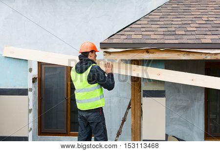 Roofer builder worker dismantling roof shingles . poster