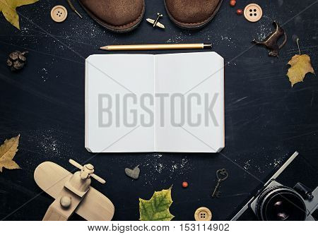 Composition of suede shoes retro camera wooden airplane yellow leaves notebook pencil on a dark scratched background. In the center of an open notebook with free space for your design. Mock up for art work.