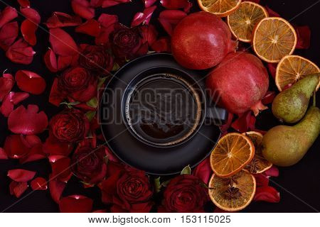 Black background filled with rosepetals, red roses, black coffee, pommegranate, pears, oranges, black coffeecup.