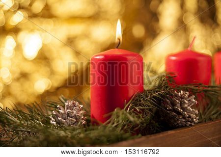 First candle burning on a red Advent wreath with golden background