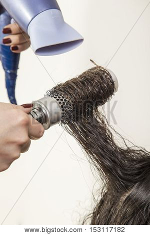 Hairdresser styling hair with blow dryer after a haircut