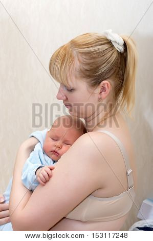 Newborn sleeping in mother's arms close up shot