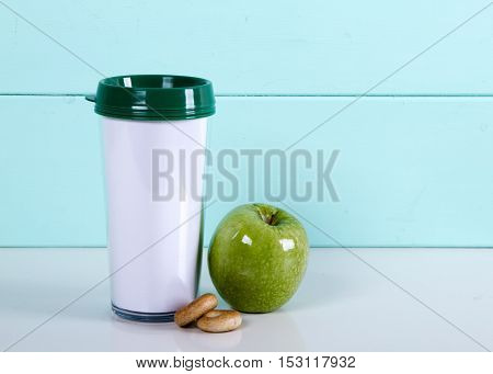 Thermocup apple bagels on a wooden blue background on the table. autumn tea