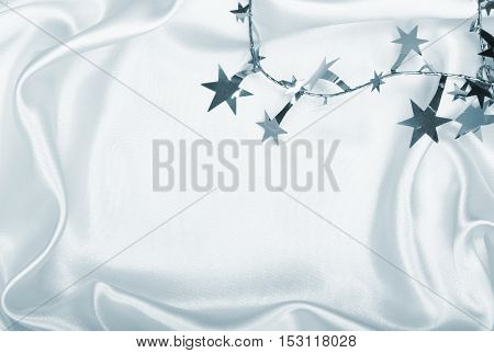 Silver stars and spangles on toned white silk can use as background