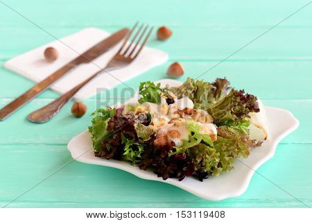 Fresh salad leaves with yogurt and nuts on a plate. Salad is prepared from radicchio, lettuce, iceberg, frieze. Diet food recipe. Fork, knife on a wooden background. Closeup