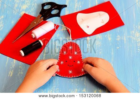 Child holds a Christmas bell toy in his hands. Child shows a felt bell. White and black threads, scissors, paper pattern, felt sheets on a wooden table. Easy Christmas art and craft idea for kids