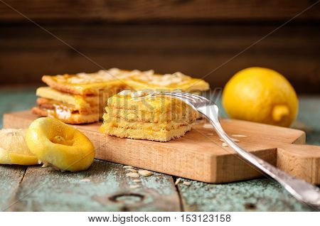 Oldfashioned imperfect layered lemon cake on wooden board closeup