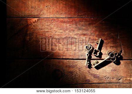 Three vintage keys on old wooden background under beam of light