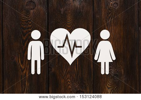 Paper man, woman and heart with pulse on dark wooden background. Love or cardiology concept. Abstract conceptual image