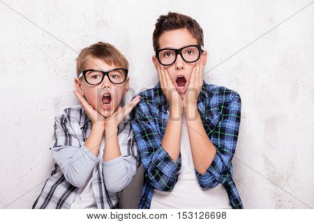Portrait of two young brothers wearing fashionable eyeglasses smiling looking at camera.