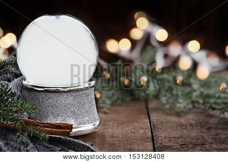 Rustic image of an empty snow globe surrounded by pine branches cinnamon sticks and a warm gray scarf. Shallow depth of field with selective focus on snowglobe.