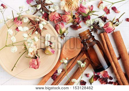 Essential oil of rose, cinnamon, anise mix. Herbal aroma beauty care. Dropper bottle, dried fragrant flowers, sticks, wooden utensils, top view background.