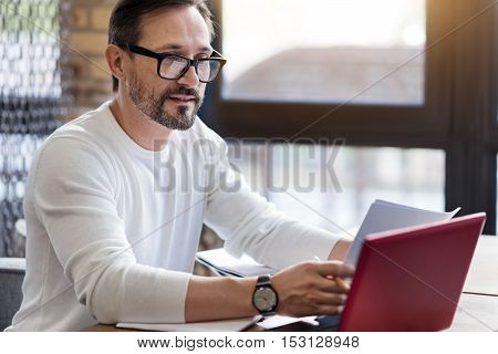 Working process. Handsome bearded man wearing gasses sitting in office and intensively using his little laptop.