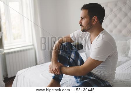 Heartbroken lonely man in pajamas on bed