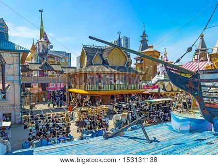 MOSCOW RUSSIA - MAY 10 2015: The replica of the wooden ship on sea made of blue timbers with the mansions and izba houses of Izmailovsky market-town on the background on May 10 in Moscow.