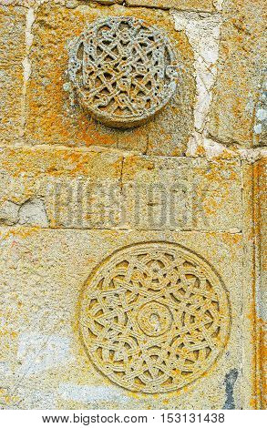 The traditional Georgian rosette carved patterns on the frontage wall of Tsminda Sameba (Holy Trinity) Church Gergeti Georgia.