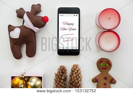 Flat view of mobile phone in the centre of cute Happy new year decoration, cones, box of glass balls, ginger man, candles, Rudolph the Red Nosed Reindeer toy. New year concept, high angle