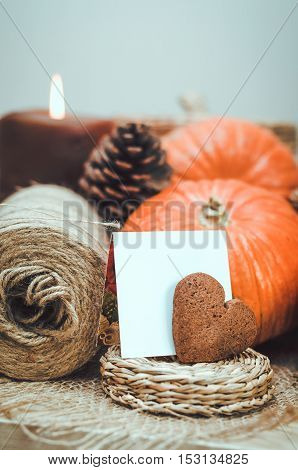 Autumn still life with orange pumpkins, brown candle, twine, cone on table craft background. Thanksgiving holliday, vintage style, rustic decor at home.