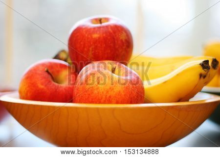 High key image of a bowl full of apples and bananas