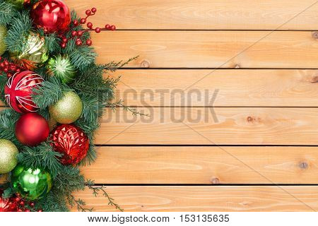 Festive pine and berry christmas garland with red and green ornaments border cedar panel background