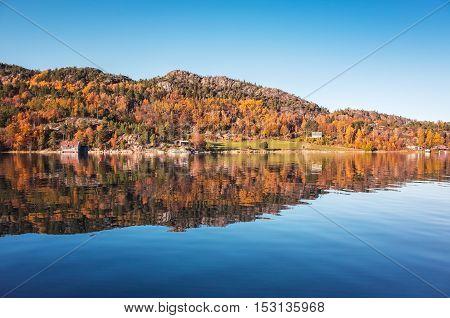 Coastal forest with reflection in still water. Norwegian landscape. Snillfjord Sor-Trondelag Vingvagen fishing camp