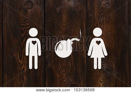 Paper man, woman and bomb with fuse on dark wooden background. Love relation concept. Abstract conceptual image