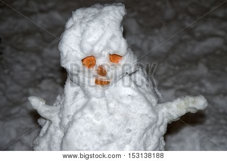 snowman with bulging eyes and hands sitting in a snowy outdoors