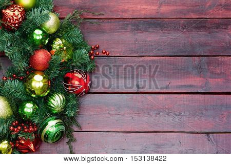 Red And Green Themed Christmas Wreath On Wood