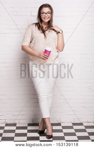 Beautiful smiling plus size female model posing in studio wearing casual clothes looking at camera.