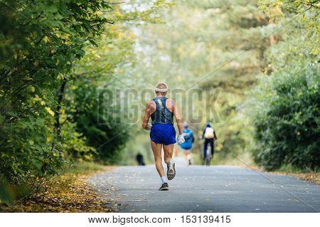 sports elderly man athlete running in autumn forest marathon