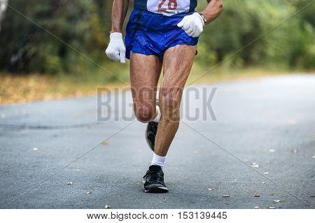 elderly man athlete running by autumn city Park marathon