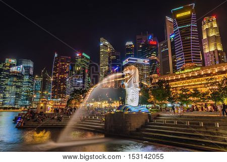 SINGAPORE-JULY 8 2016: Merlion statue fountain in Merlion Park and Singapore city skyline at night on July 8 2016. Merlion fountain is one of the most famous tourist attraction in Singapore.