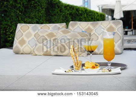 cocktail and snack appetizer serve at outdoor bed - evening sunlight