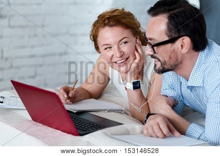 Lifelong sweetheart. Smiling woman looking at bearded man watching laptop while lying on bed.