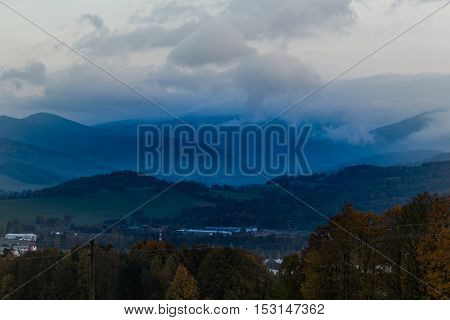 Summer weather phenomenon. Seasonal landscape with morning fog in valley. Clouds drenched valley below the level of the mountains. Sunrise over creeping clouds