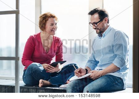 Enjoying sunlight. Pretty smiling ginger woman holding laptop near bearded man making motes with pencil while sitting on windowsill.