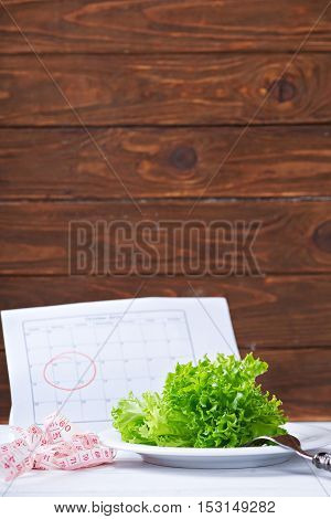Diet concept. Fresh salat, and measurement tape - diet and healthy eating concept. Starting new life from monday. On a wooden background