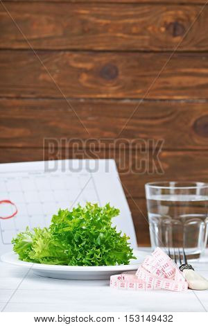 Diet concept. Fresh salat, water and measurement tape - diet and healthy eating concept. Starting new life from monday. On a wooden background