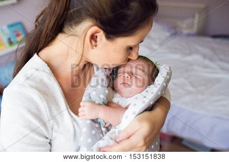Beautiful young mother holding her newborn baby son in her arms, kissing him. Close up.